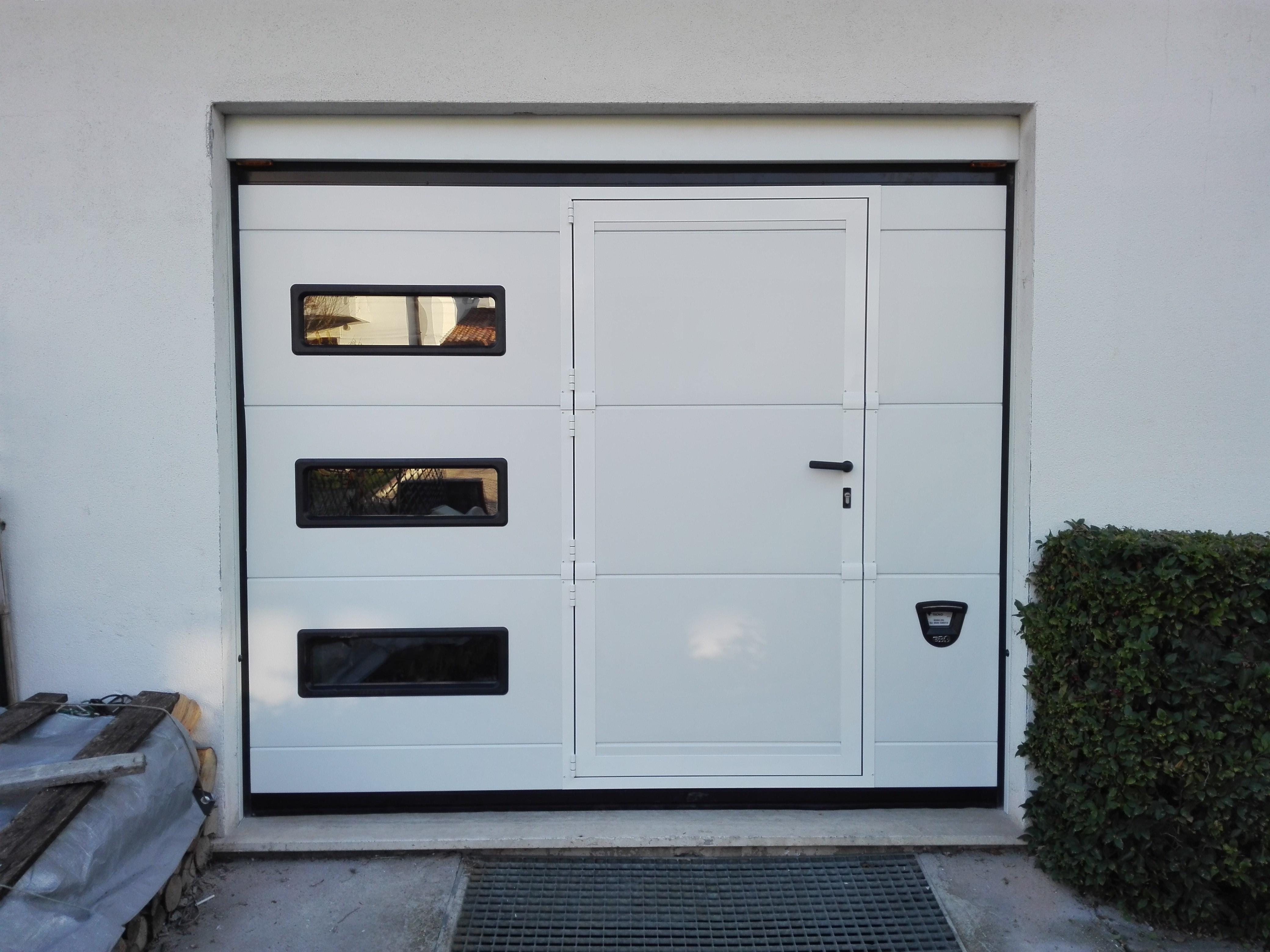 Portone sezionale con 3 oblò in verticale e porta pedonale inserita